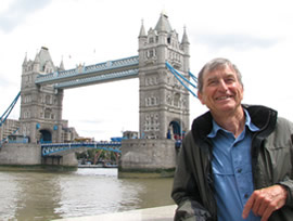 photo of author standing beside the Thames River in London with the Tower Bridge in the background